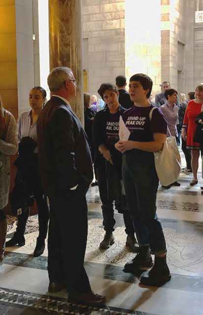 In the background, people are standing in the capitol building rotunda, talking to each other and their state senators. In the foreground, State Senator Dan Hughes and OutNE volunteer Mar Lee talk about LB627