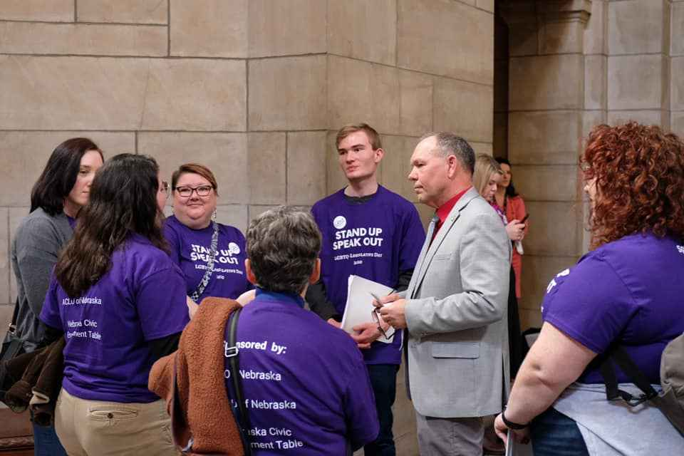 lobbyists in purple shirts talk to their state senator