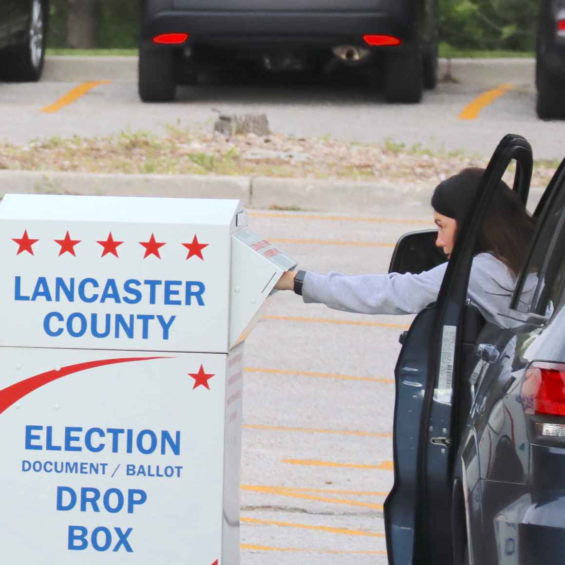 A voter drops a ballot in an election drop box.