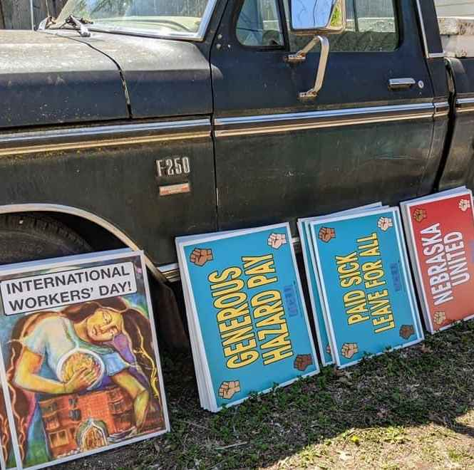 Workers' rights posters lean against a pickup truck.