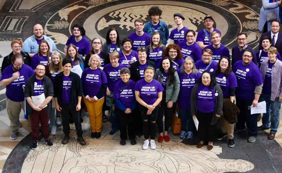 Photo taken from above and angled down. Nebrakans wearing purple shirts pose in the Nebraska Capitol Rotunda