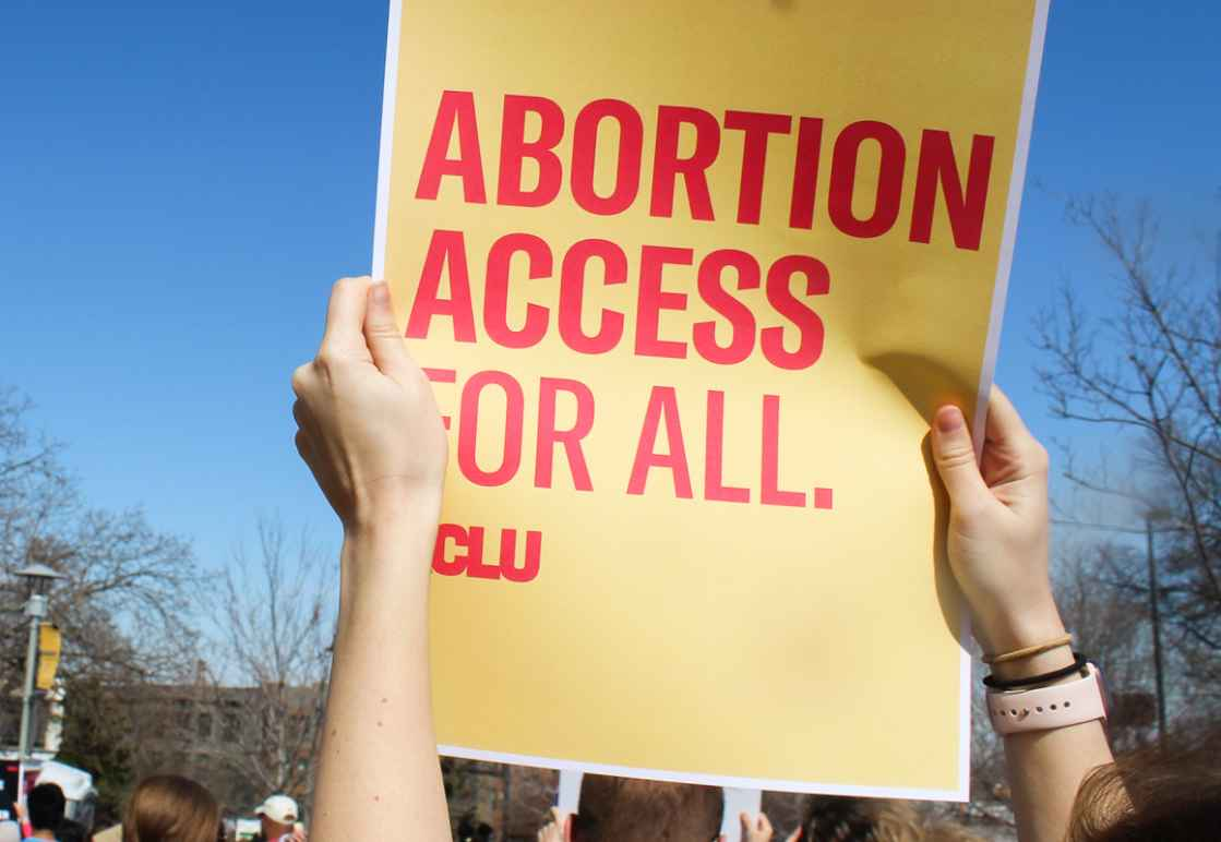 """A protester holds a sign reading """"Abortion access for all."""""""