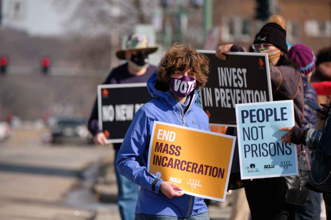 """Protesters stand alongside a Lincoln street, holding signs that read """"End mass incarceration"""" and """"People not prisons."""""""