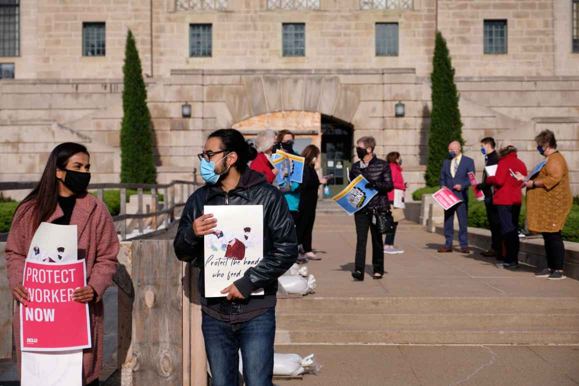 Community members stand at the east entrance of the Nebraska State Capitol, holding signs encouraging protections for essential workers.