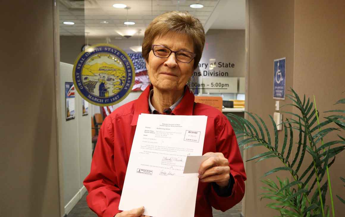 Campaign co-chair and former State Sen. DiAnna Schimek displays a copy of filed paperwork outside of the Nebraska Secretary of State's Office.