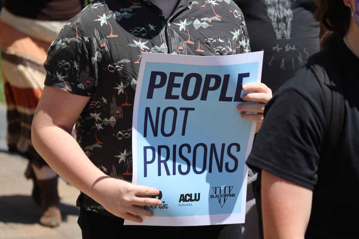"""A protester holds a sign reading """"People not prisons."""""""