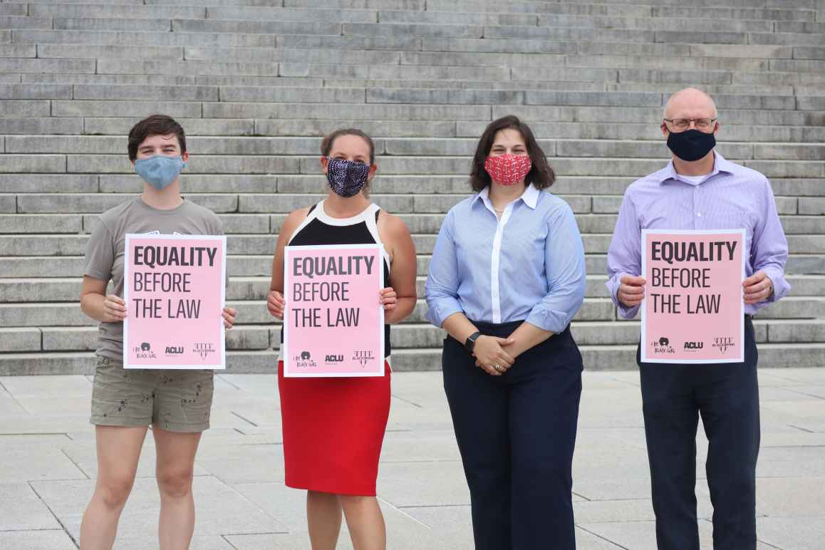 "Four ACLU staff members stand outside the Nebraska State Capitol, three of whom are holding signs reading ""Equality Before the Law."""