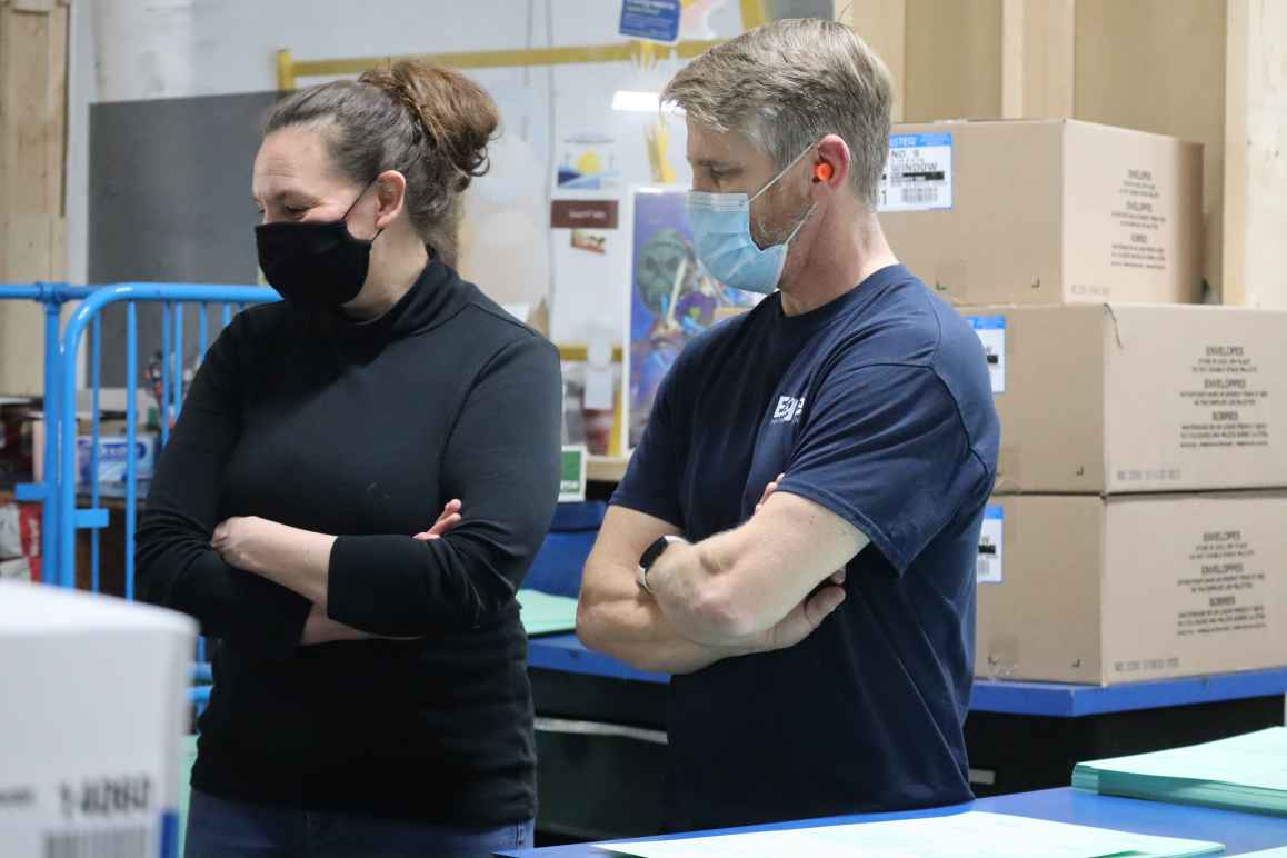 ACLU of Nebraska Executive Director Danielle Conrad and Eagle Printing & Sign employee Rick Hallet look at boxes of printed ballot applications. The ACLU is sending more than 300,000 early voting ballot applications to registered voters in Lincoln and Oma