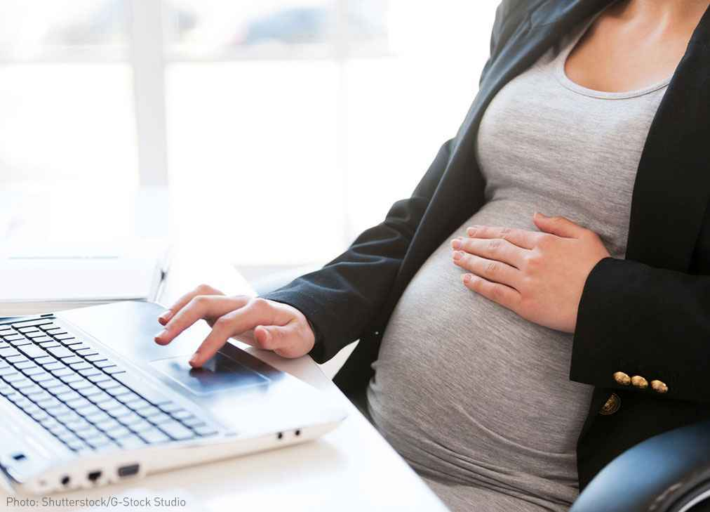 Pregnant woman at desk