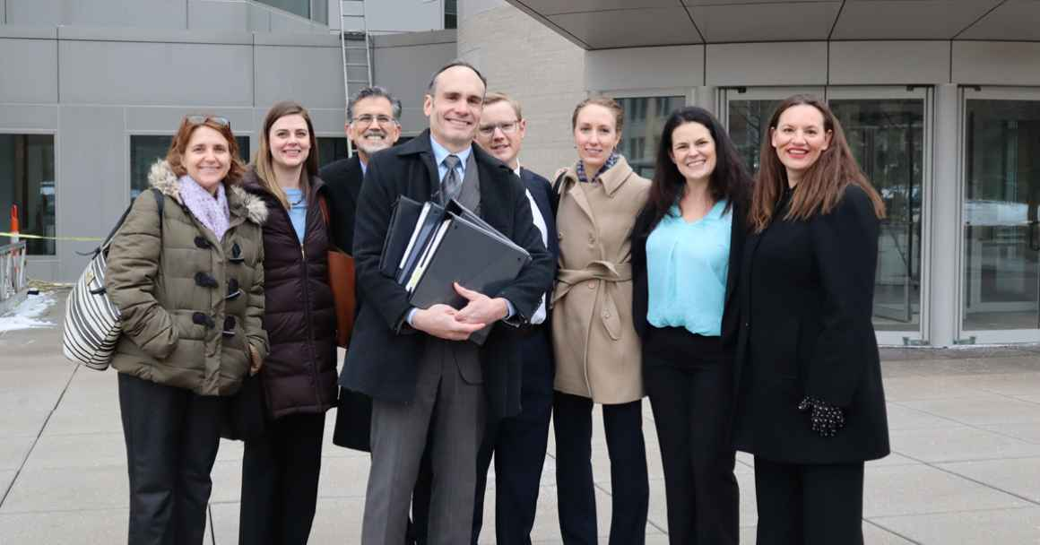 The legal team stands in front of the Roman L. Hruska Federal Courthouse.