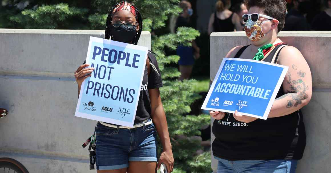 "Protesters hold signs reading ""People not Prisons"" and ""We Will Hold You Accountable"""